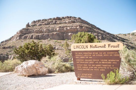 """The sign says """"Gypsum from the San Andreas Mountains is being carried down and deposited in the Tularosa Basin, creating the White Sands."""""""